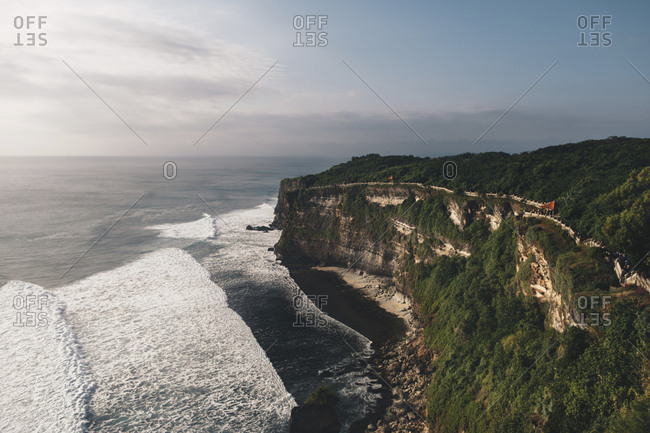 Scenic view of cliff by sea against cloudy sky