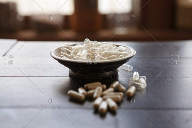 Close-up of capsules with bowl on wooden table