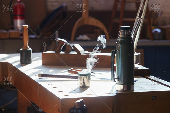 Insulated drink container with work tools on table in workshop