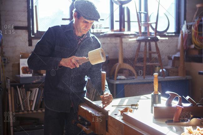 Carpenter using chisel and mallet at workshop