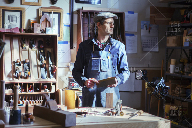 Carpenter holding handsaw looking away while standing by table in workshop