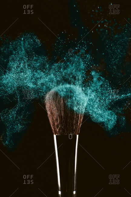 Close-up of make-up brush with turquoise face powder against black background