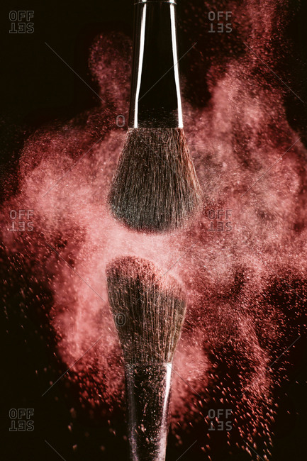 Close-up of make-up brushes with red face powder against black background