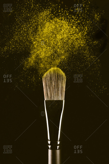 Close-up of make-up brush with yellow face powder against black background