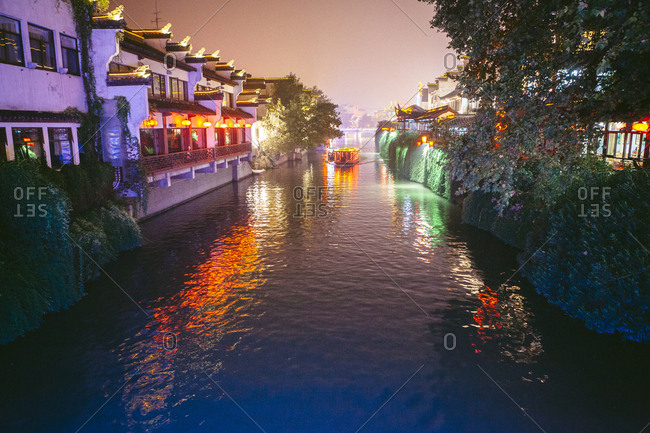 Boat on canal amidst illuminated buildings in city at dusk