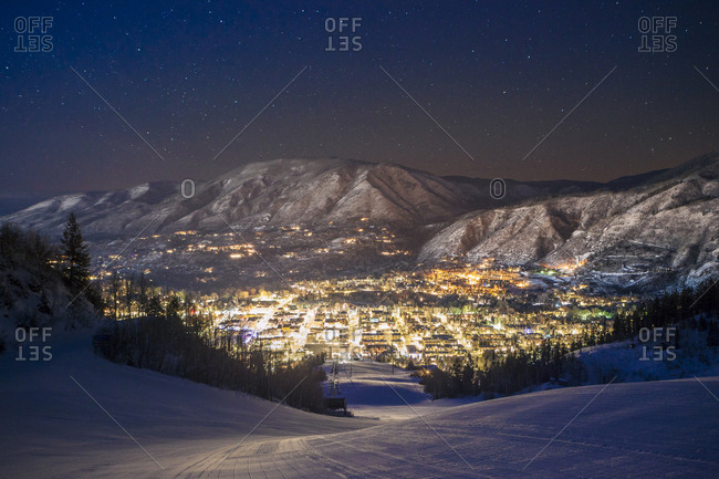 Illuminated cityscape by mountains seen from ski slope at night