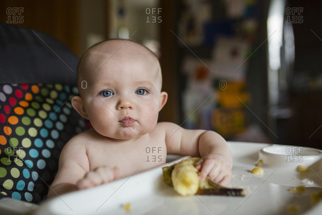Portrait of cute shirtless baby girl with banana sitting on high chair
