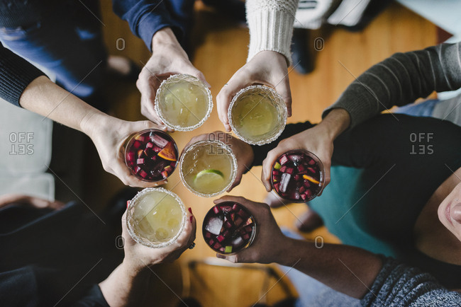 Overhead view of friends toasting drinks during social gathering at home