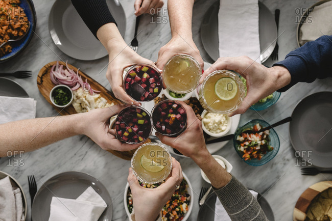 Cropped hands of friends toasting drinks at table
