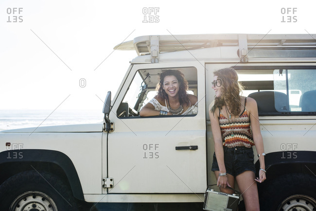 Happy woman looking at friend sitting in off-road vehicle during sunny day