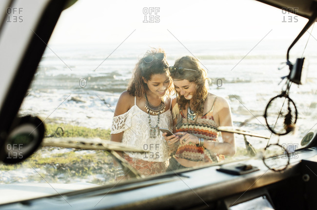 Happy friends using mobile phone at beach seen through windshield