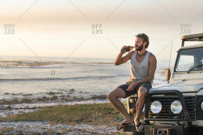 Man drinking beer while sitting on off-road vehicle at beach during sunset