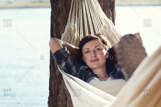 Portrait of woman relaxing on hammock by tree at lakeshore