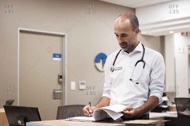 Doctor preparing reports while working in hospital