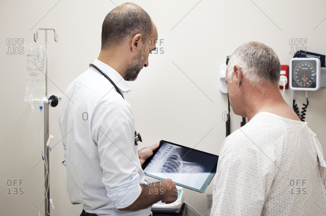 Doctor showing x-ray reports in tablet computer to patient at hospital