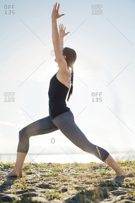 Woman practicing warrior pose at beach against clear sky