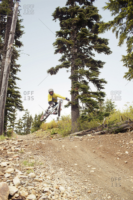 Low angle view of man mountain biking on dirt road in forest