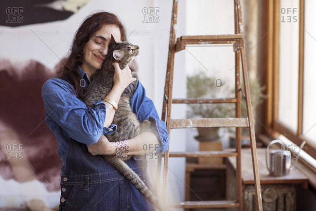 Smiling artist embracing cat while standing in workshop