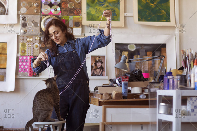 USA, New York, New York City - February 14, 2017: Happy female artist playing with cat in workshop
