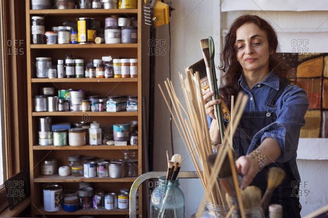 Artist holding paintbrushes in workshop