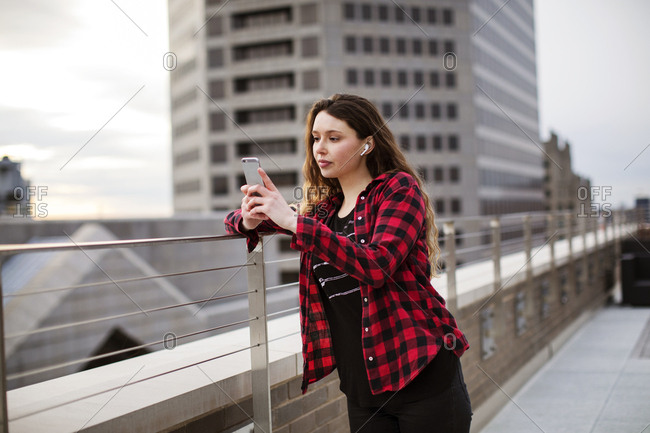 Young female using smart phone while standing by railing at terrace