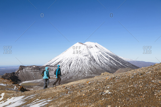 Female friends hiking at Mt Ngauruhoe against clear blue sky on sunny day
