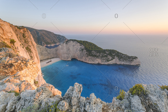Scenic view of cliff by sea against clear sky during sunset