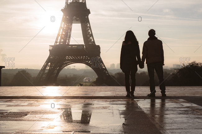 Silhouette couple looking at Eiffel Tower against sky during sunrise