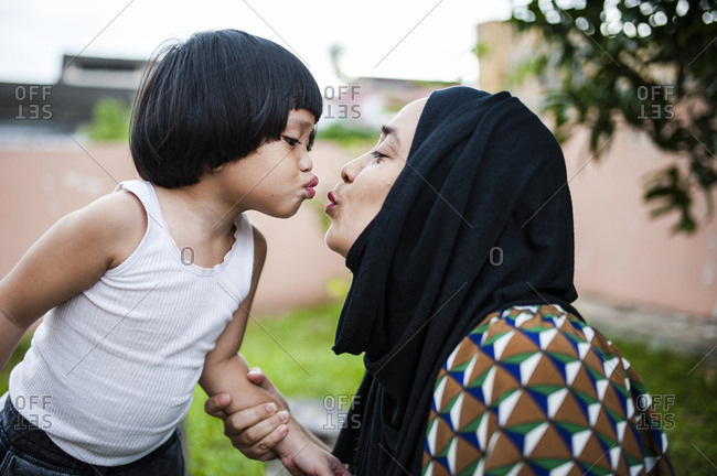 Playful mother and daughter puckering lips in backyard