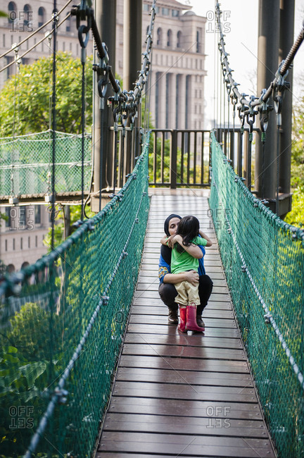 Mother and daughter embracing on rope bridge