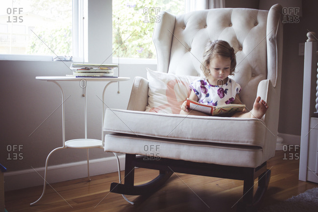 Girl reading picture book while sitting on rocking chair at home