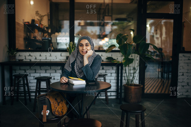 Portrait of woman with books sitting in cafe