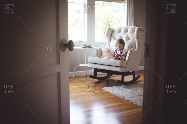 Girl reading picture book while sitting on rocking chair at home seen through doorway