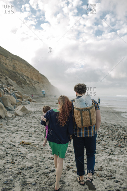Rear view of family walking at rocky beach against cloudy sky