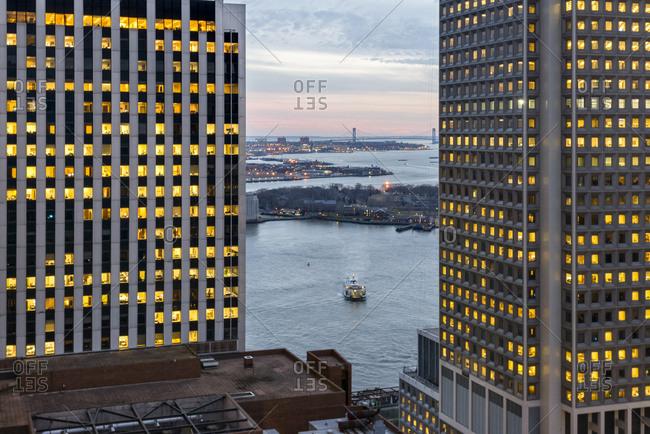 Large glass office windows overlook the New York harbor