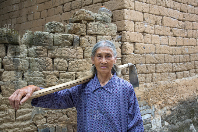Guilin, China - October 16, 2012: Senior woman holding a garden tool over her shoulder