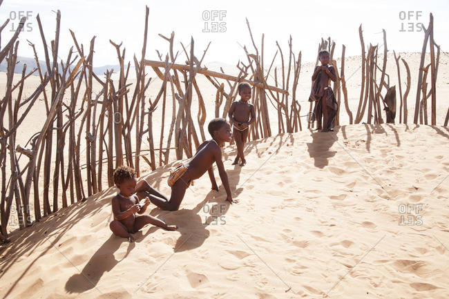 Namibia - January 15, 2008: Himba tribe boys playing in sand in a livestock corral