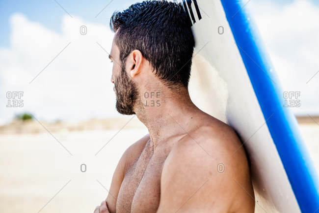 Surfer in front of his surfboard looking away