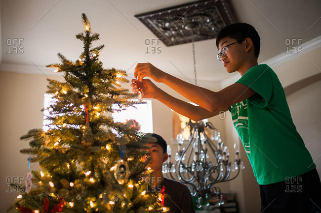 Teen brothers decorating Christmas tree