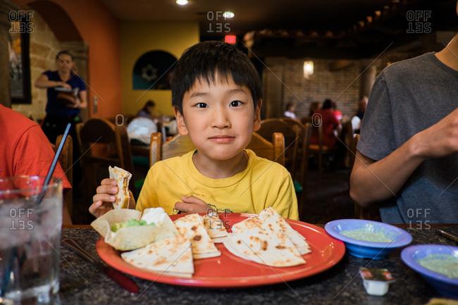 Young boy eating quesadillas at restaurant