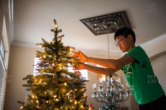 Teen boy decorating Christmas tree