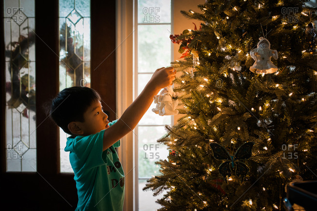 Young boy hanging an ornament from branch on Christmas tree