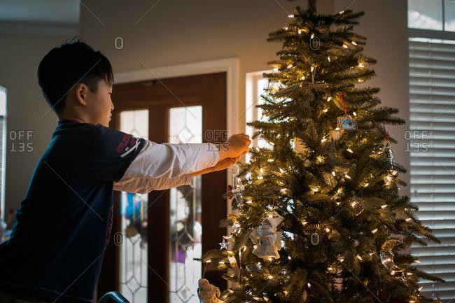 Boy hanging an ornament on Christmas tree