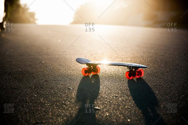Children's skateboard in street at dusk