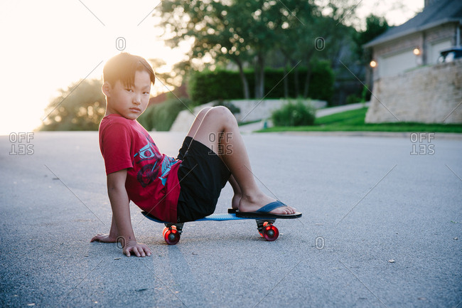 Young boy sitting on his skateboard in street