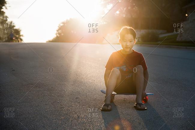 Portrait of an adolescent boy sitting on skateboard in street