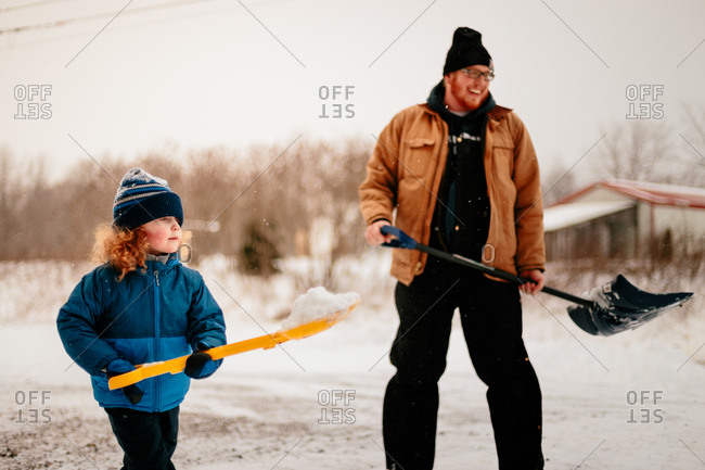 Father and son with curly red hair shoveling driveway