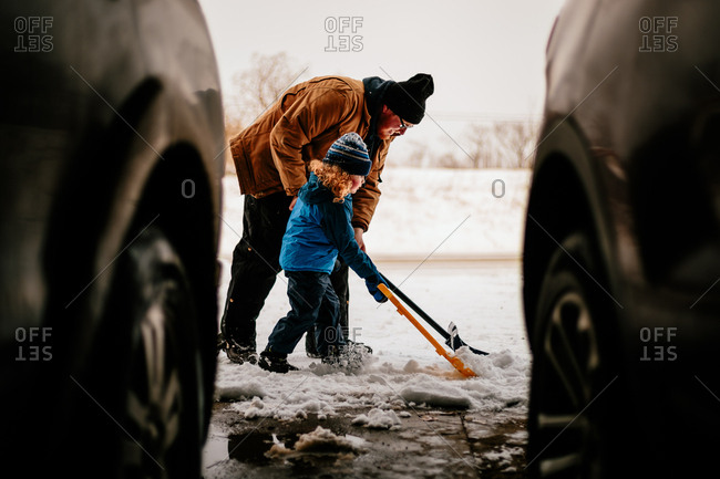 Father and son shoveling driveway