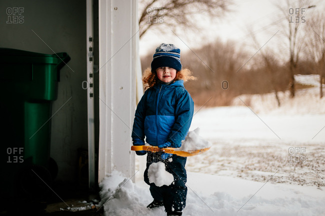 Child with curly red hair shoveling snow