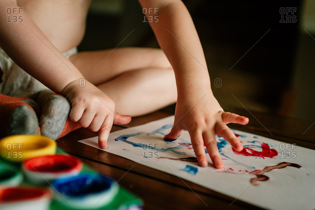 Child finger painting while sitting on floor